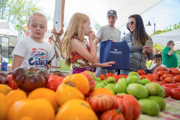 family buying vegetables at farmers market