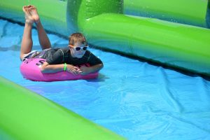 A young boy on an innertube skims across a colorful slip and slide