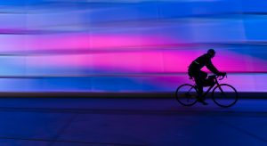 silhouette of a person riding a bike with a neon blue and pink background