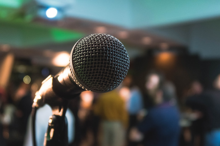 A microphone stand in front of a crowd.