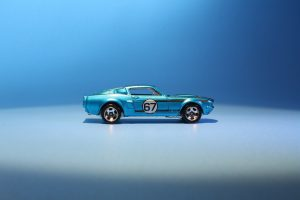 Blue die cast car painted with a number 87 sits in front of a blue backgroun.