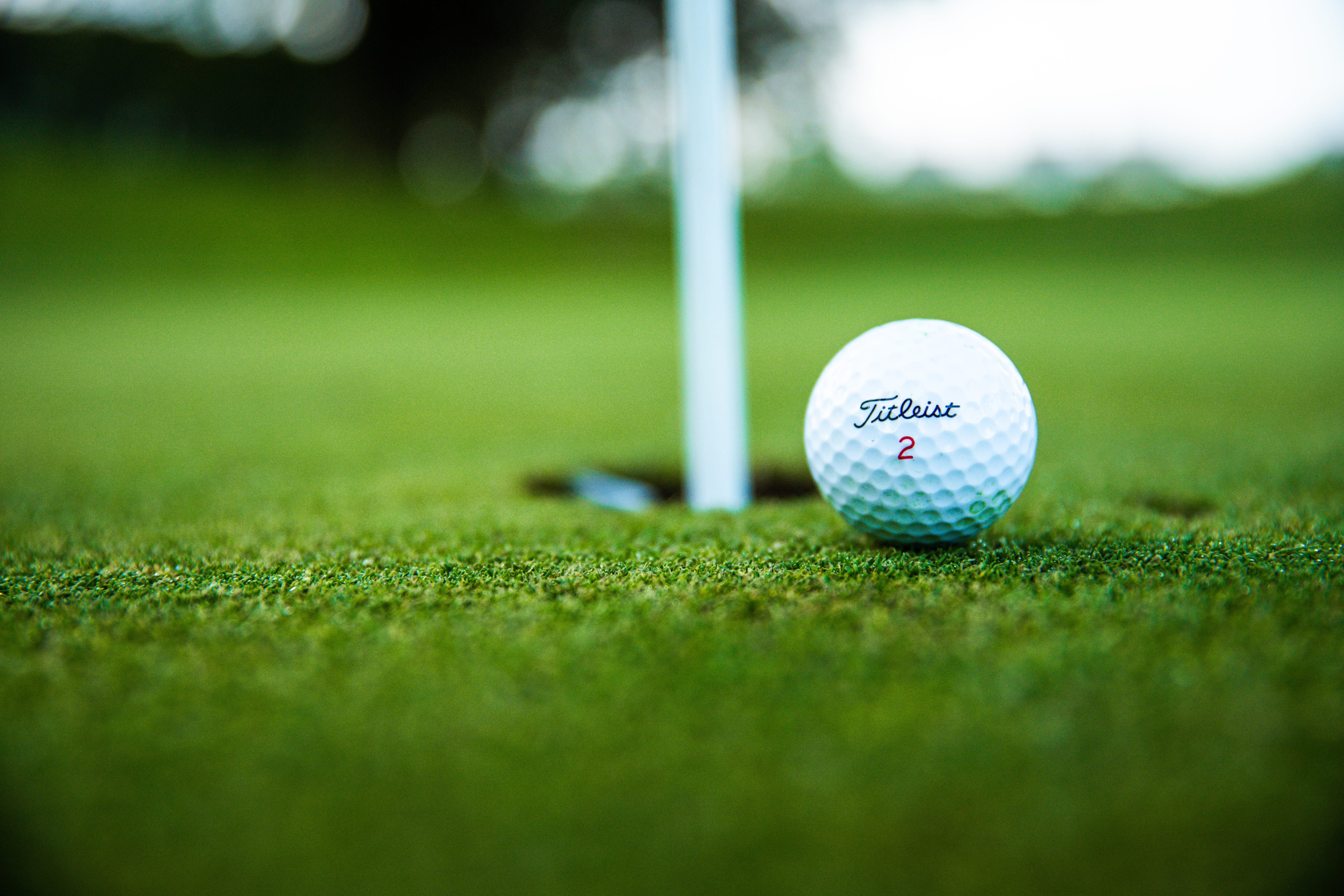 A white golf ball sits on the green while it balances on the edge of a whole in the ground with a white pole sticking up