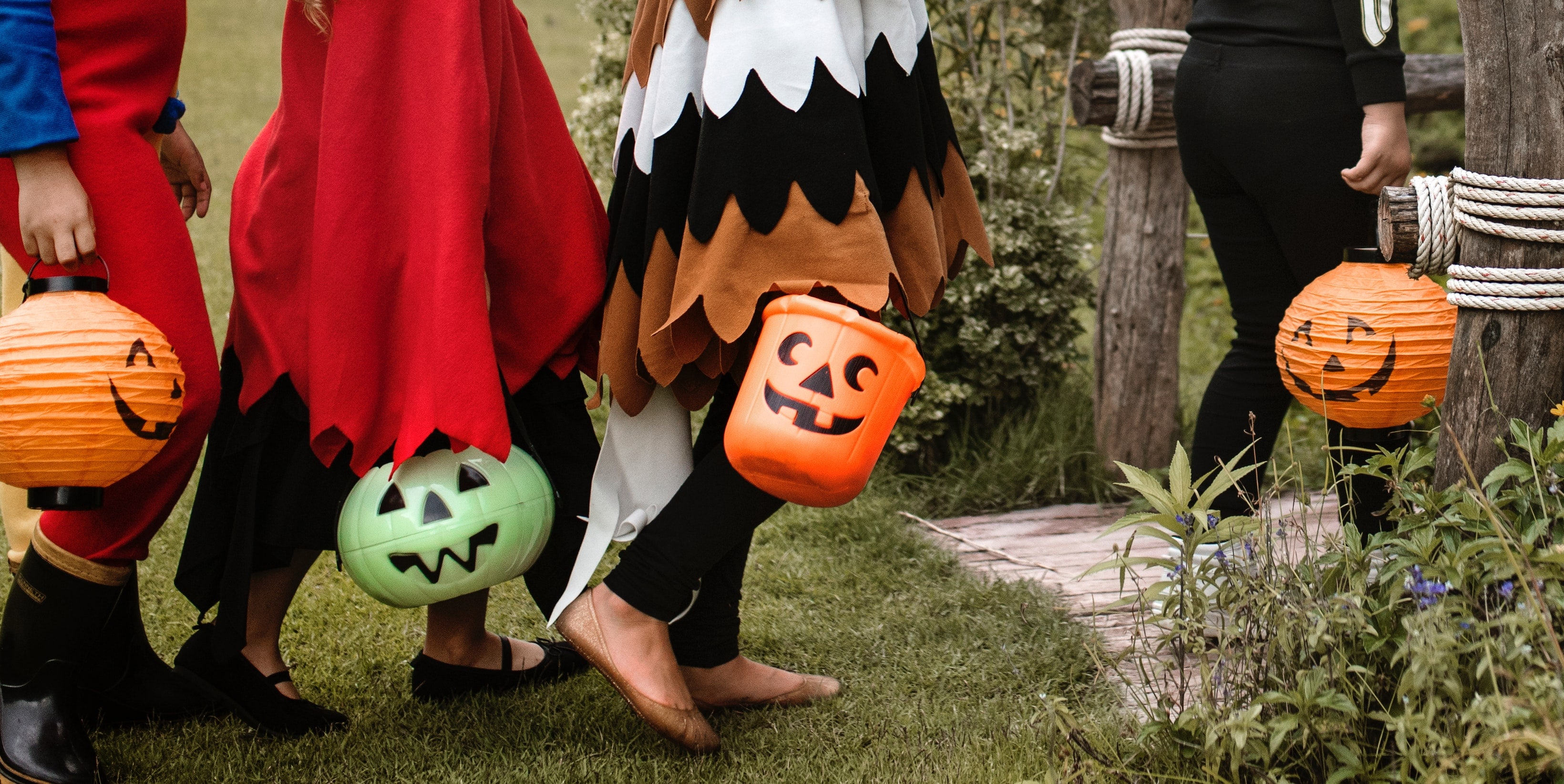 Four children dressed in halloween costumes carry plastic jack-o-lantern buckets as they walk on the grass