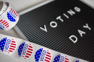 "A roll of patriotic stickers with the words ""I Voted"" sits on top of a black board with the words ""Voting Day"" written across it."