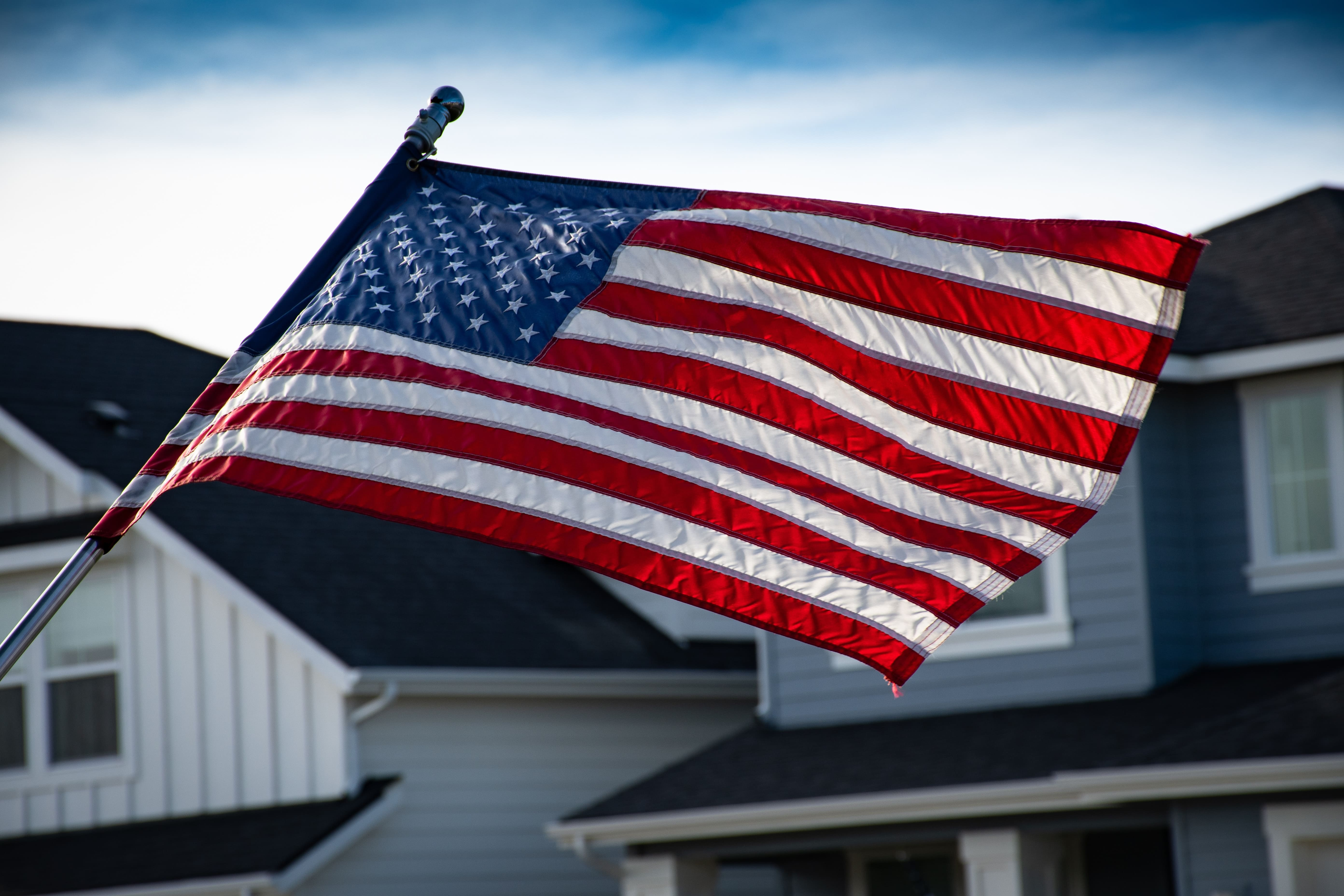 An American flag blowing in the wind with a row of homes in the background