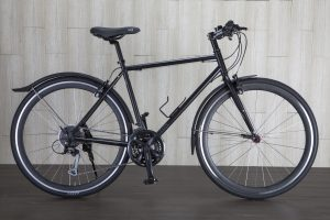 A bicycle with a black bike frame sits in front of a wall with light gray wooden panels and dark wood floors