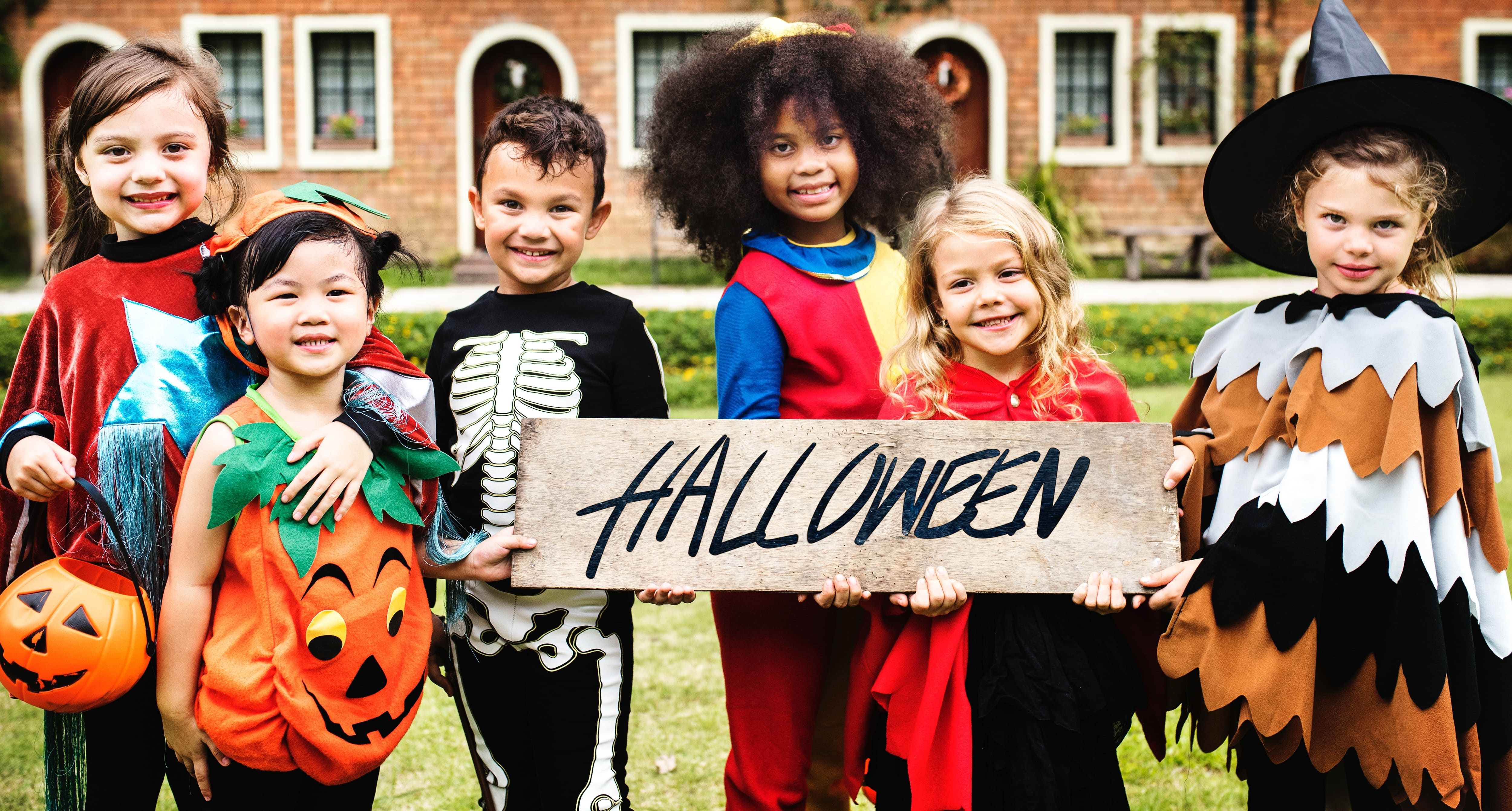 "A group of six children dressed in various Halloween costumes stand outside holding a wooden sign that says ""Halloween"""