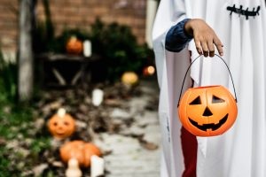Child dressed in costume holds out a pumpkin pail during a stop on the trick-or-treat trail