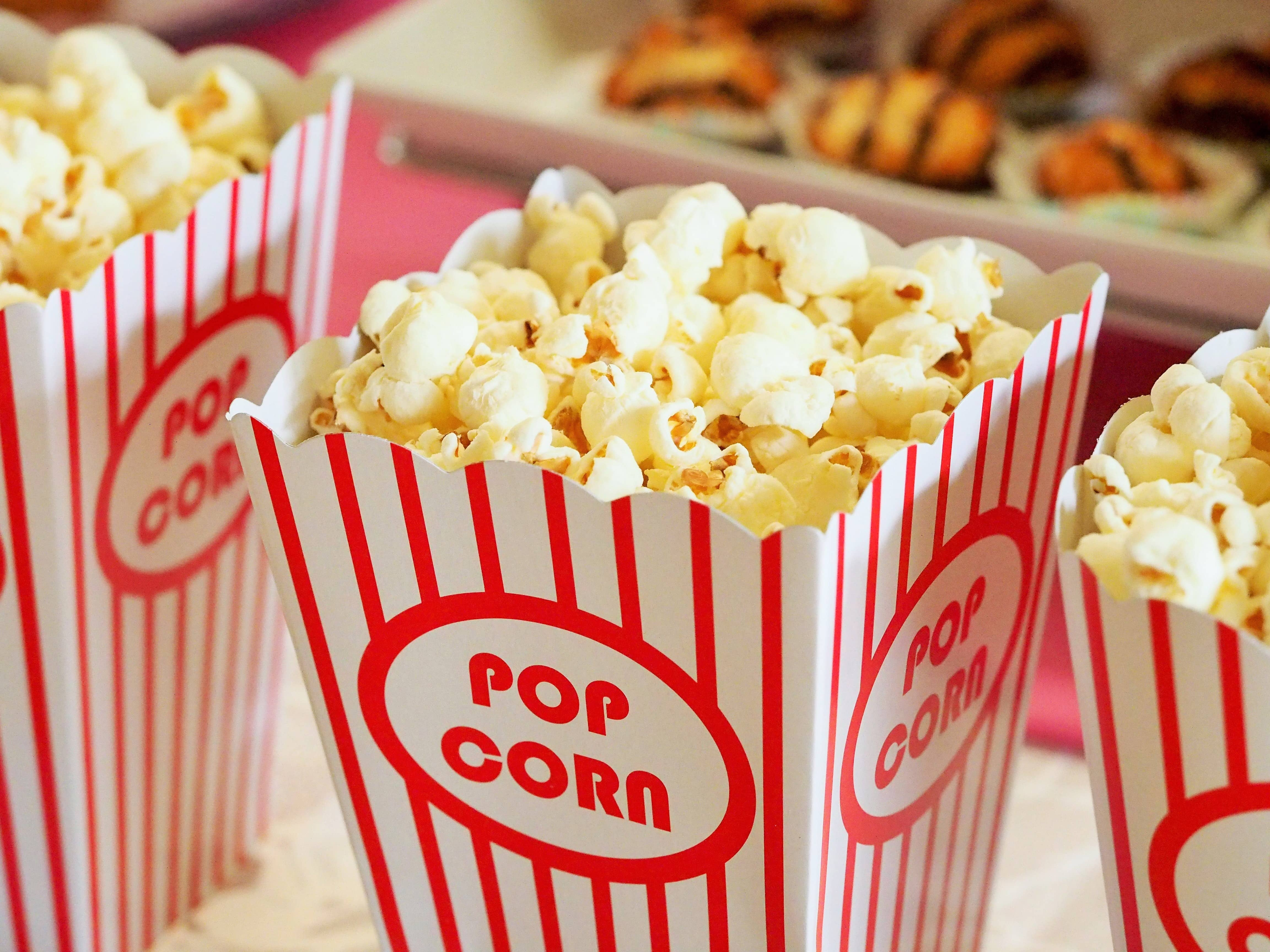 A red and white striped popcorn box filled with popcorn