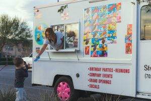 A woman hands a child a popsicle from the Street Freeze ice cream truck
