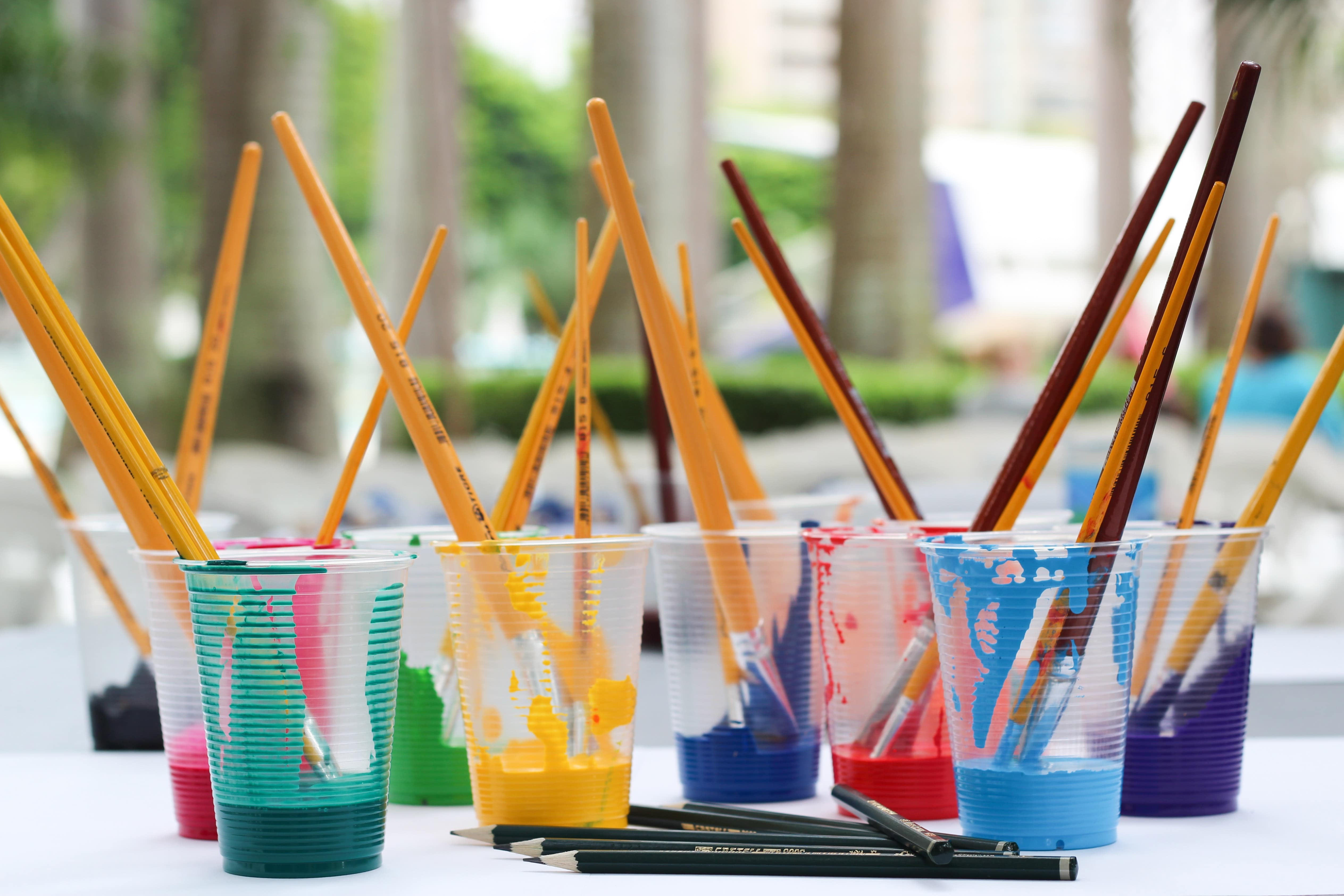 Cups of different colors of paint and brushes sit on a table