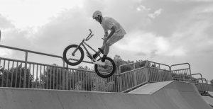A man performs a BMX bike trick on a ramp