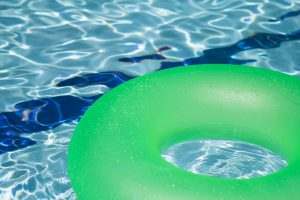 A green pool floatie floats in the water during the Mighty Medley event