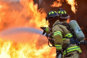 Two firefighters put out a fire