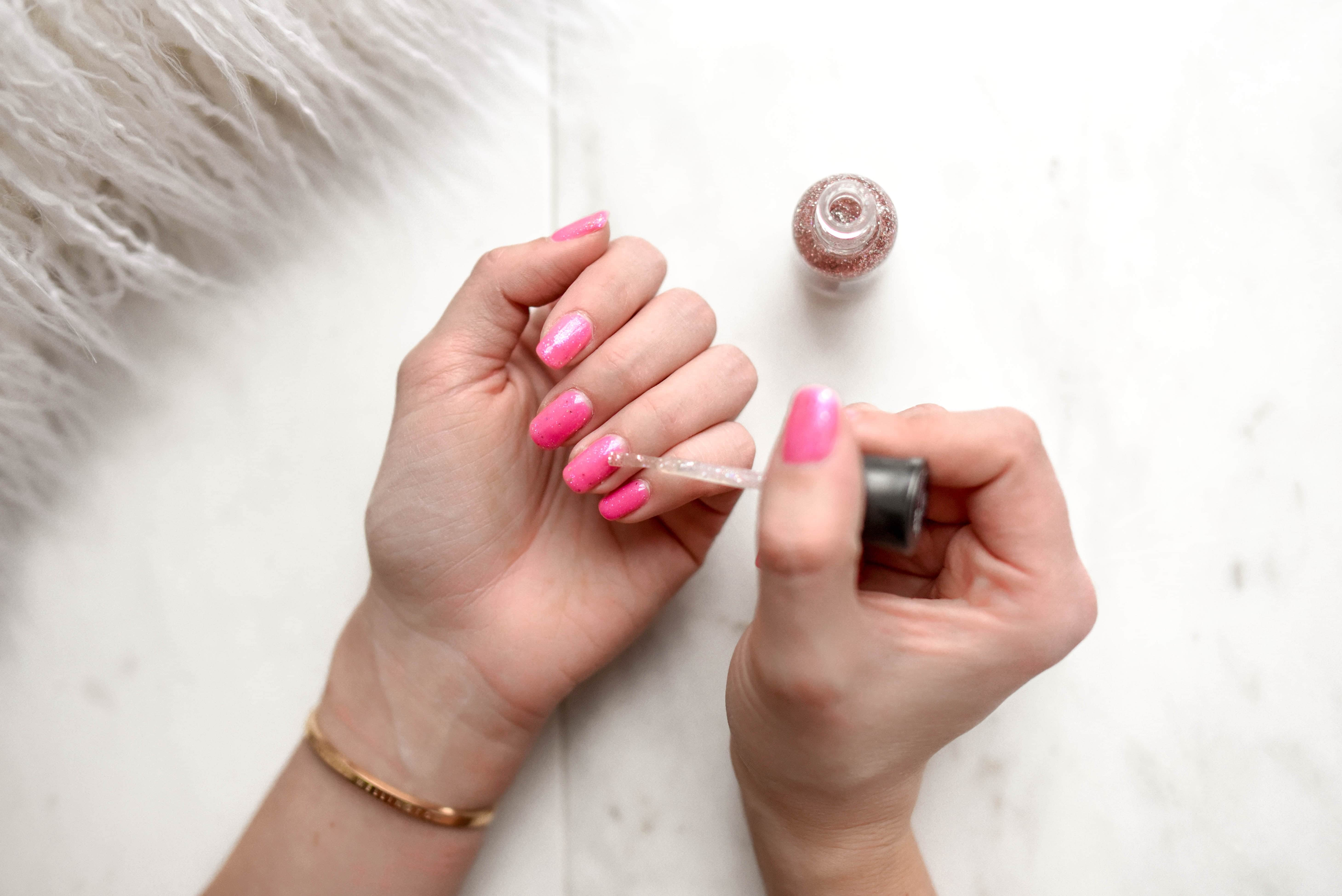 A woman puts pink nail polish on her nails