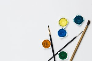 Different colors of paint and paint brushes on a white background