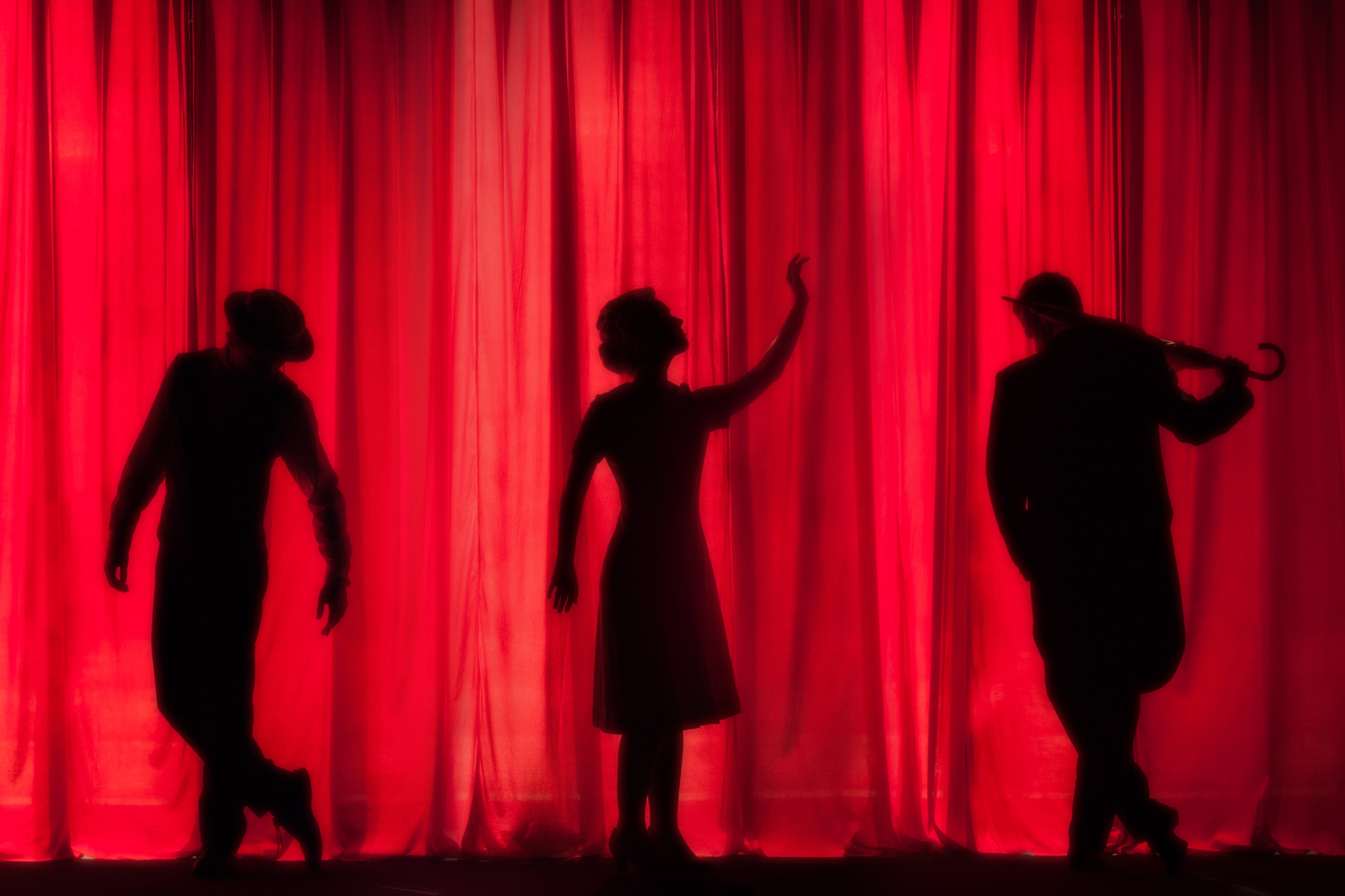 Three actors stand onstage and perform for an audience