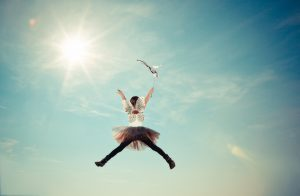 Child with fairy wings and skirt jumps into the air