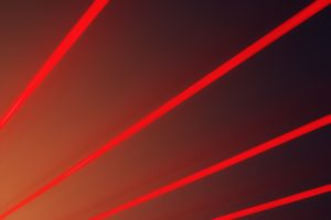 Red light beams on a black background