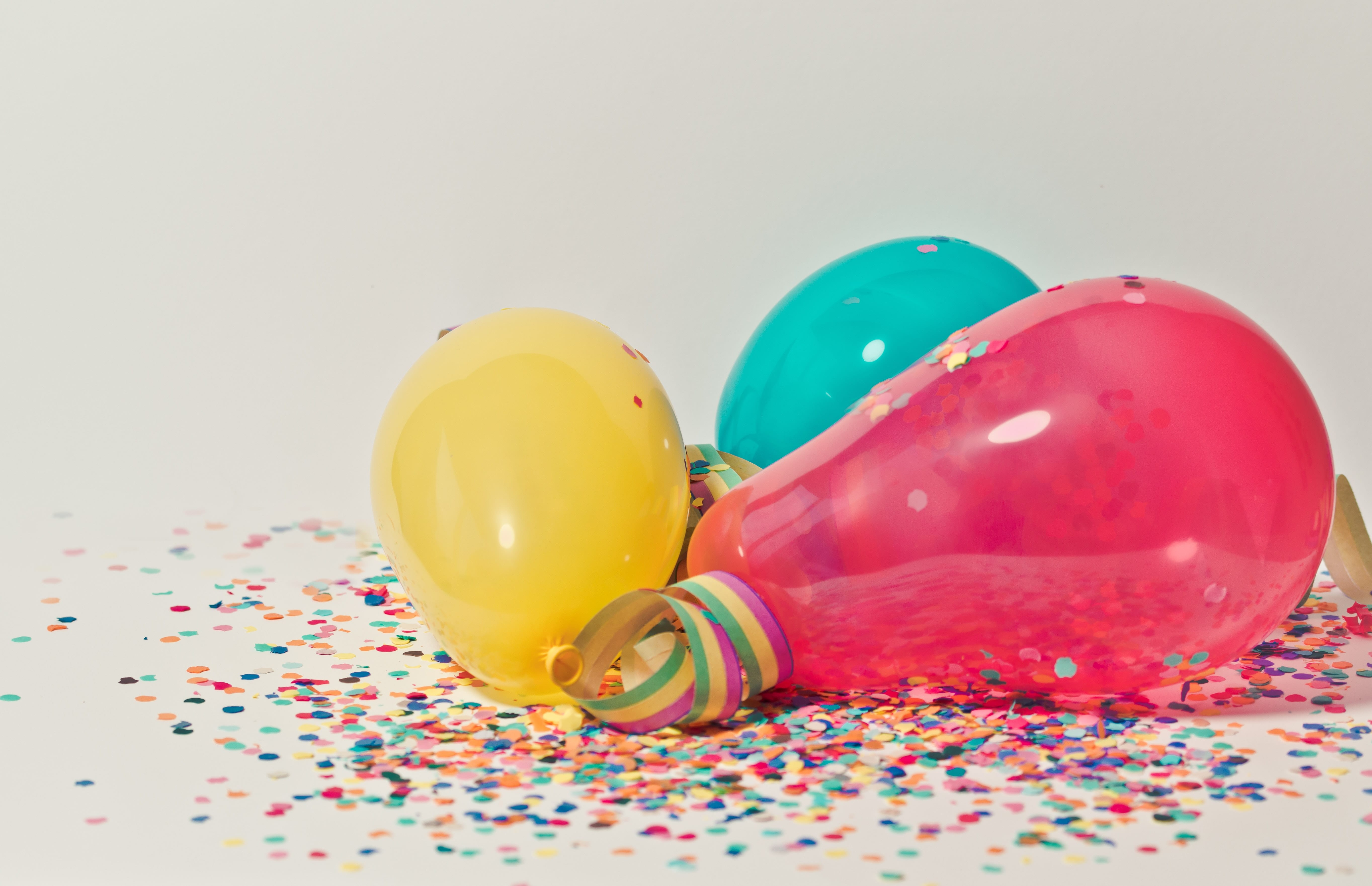 Yellow, pink, and blue party balloons lay on top of multi-colored confetti