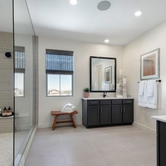 Master bathroom with glass door shower and two sinks.