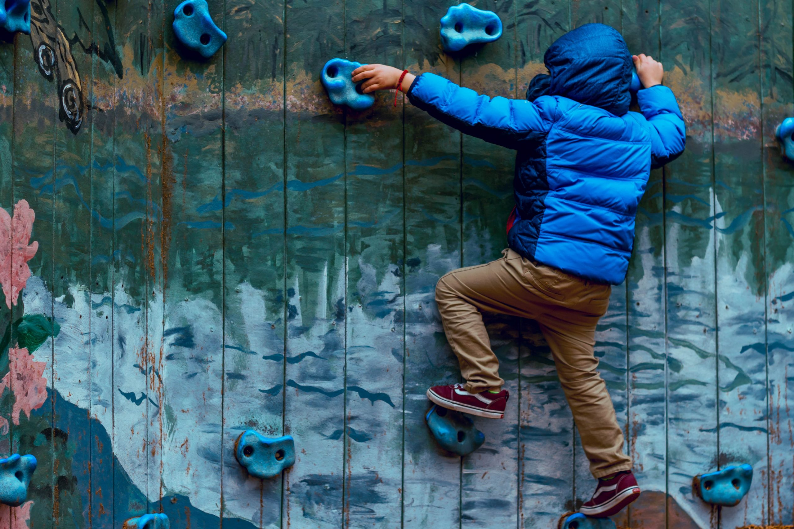 A boy climbs a rock wall with a mountain scene painted in the background.