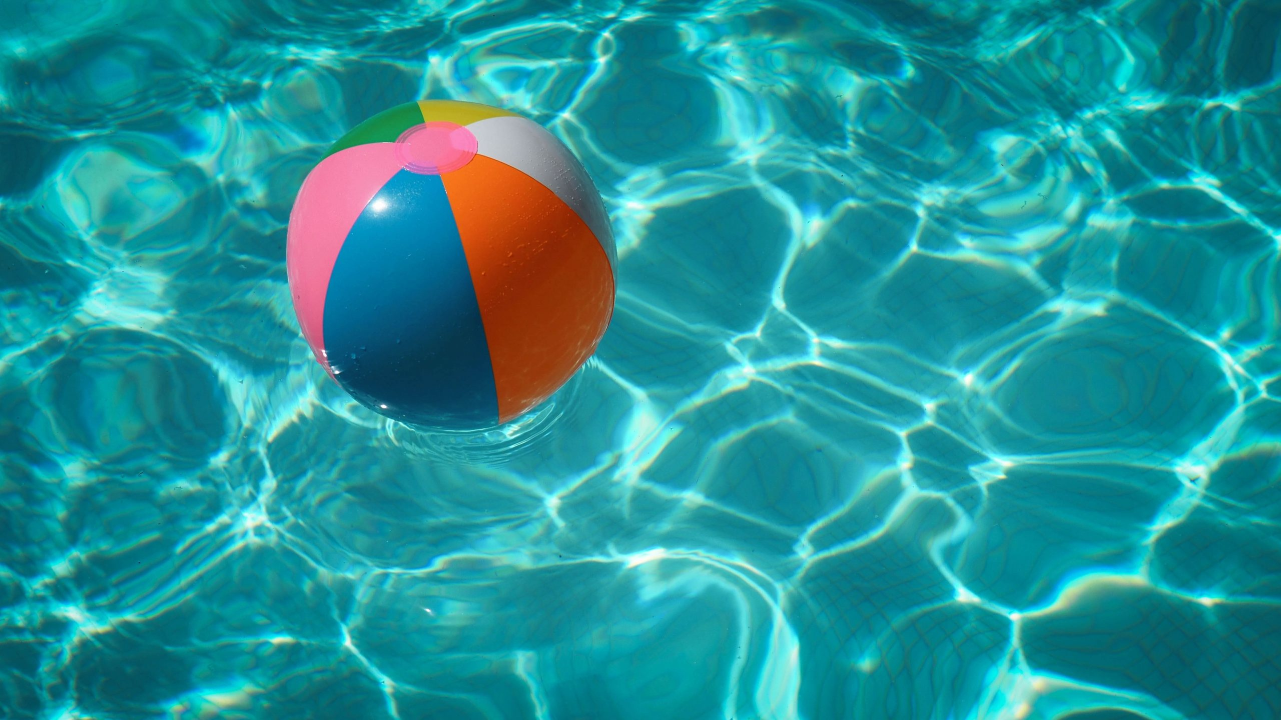 A multi-colored beach ball float in a pool