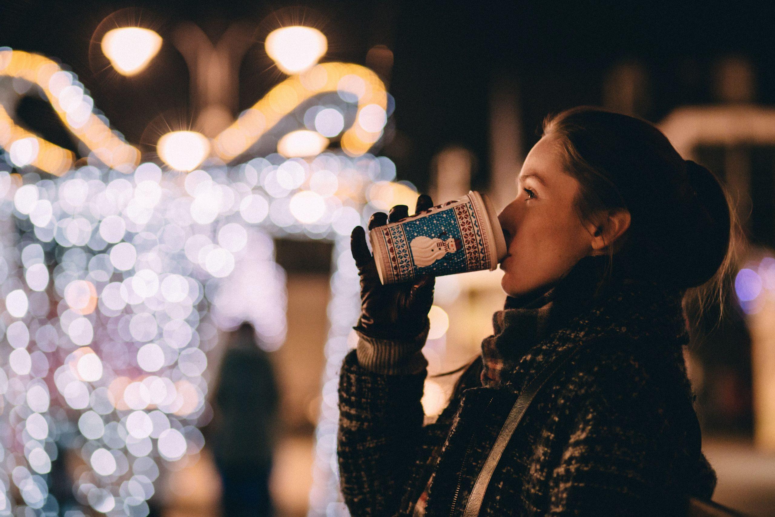 Woman enjoys hot beverage while looking at holiday lights