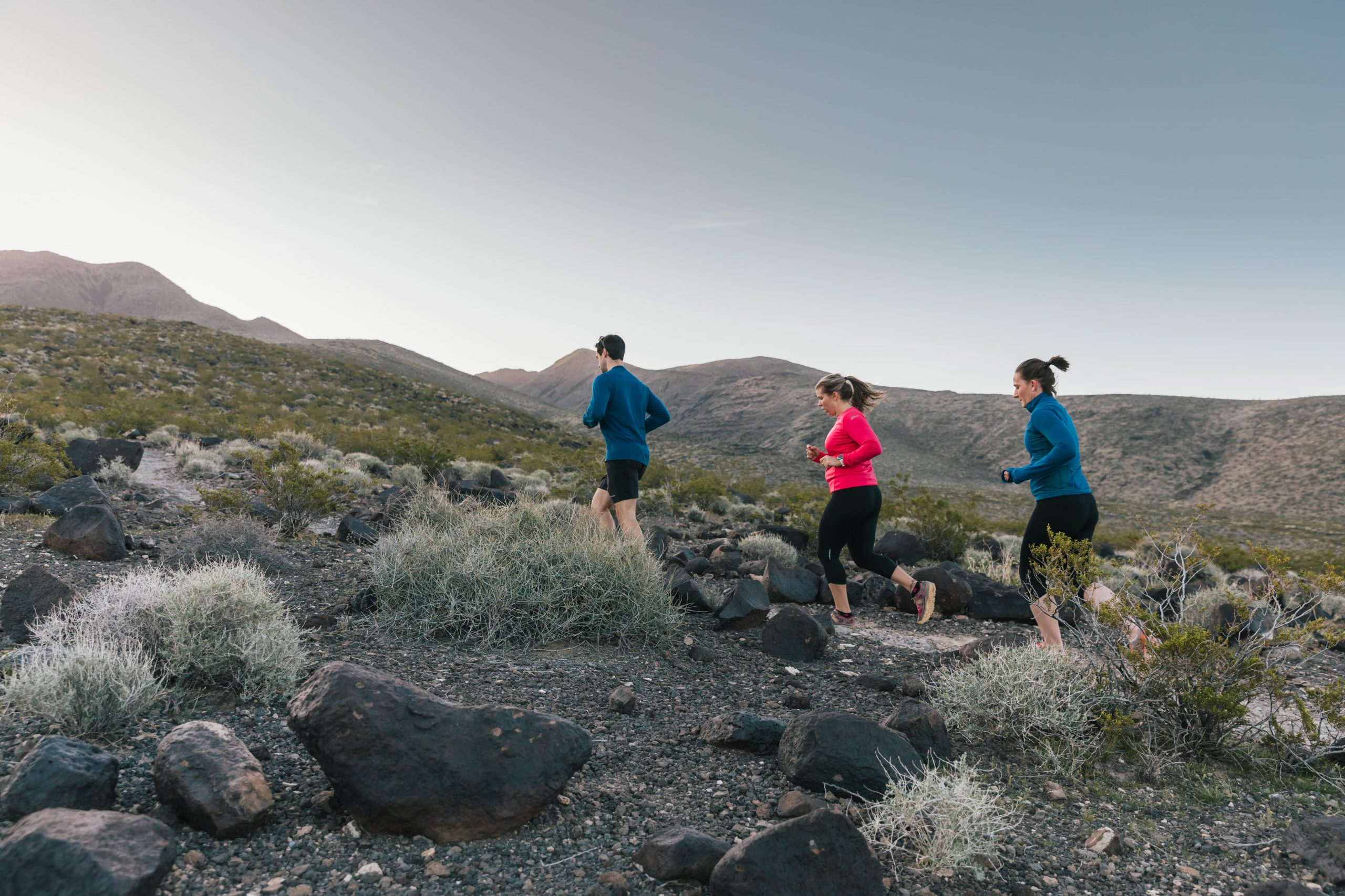 Two women and a man run on a trail